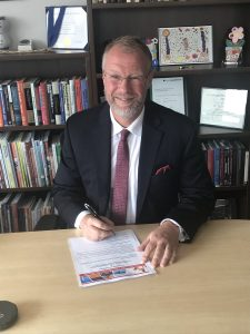 President Tim Loreman signs the statement of adoption of the Okanagan Charter