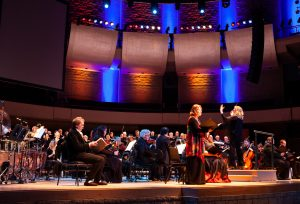 Conductor Danielle Lisboa in front of Concordia Symphony Orchestra on stage